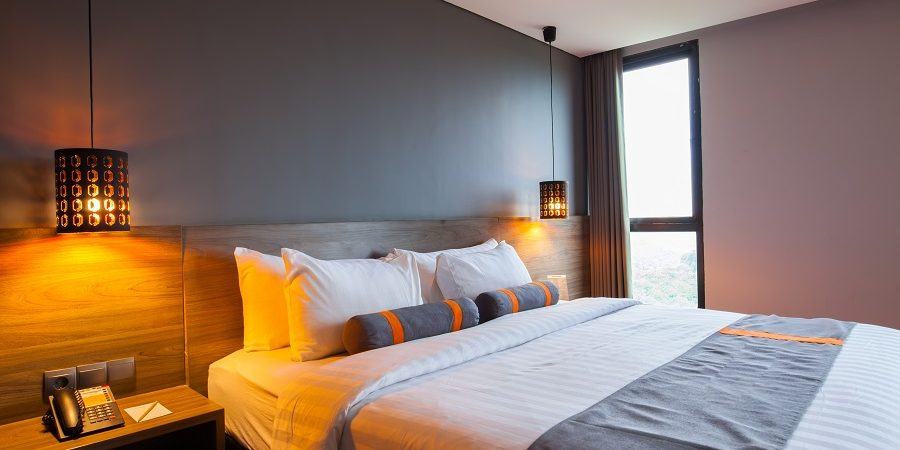 Interior of modern bedroom at hotel with white bed and pillow
